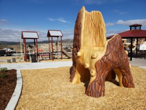 Outdoor Playtime park play area playground, tree play element, and pavilion
