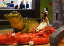 young girl playing on playtime dragon structure at lakeside shopping center