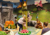 kids playing on fairytale themed playtime play area structures with parents seated looking on lakeside shopping center