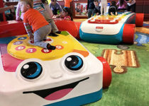PLAYTIME Fisher Price play area kids playing on phone