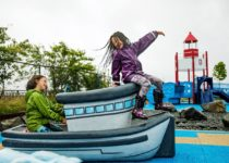 Two little girls playing on Playtime boat play element