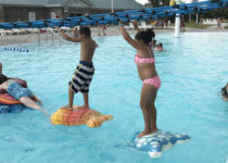 Kids having fun standing on Playtime water float features at pawnee plunge