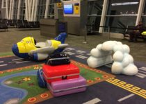 Plane, cloud and suitcase figures in airport play area by PLAYTIME