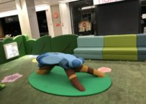 Indoor Playtime play area at shopping center with bug on branch play elements and seating in background