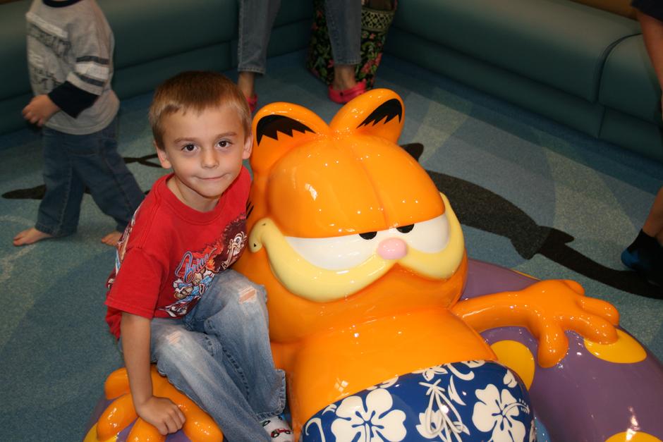 Child sitting on Garfield PLAYTIME sculpture