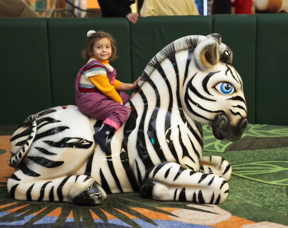 Child sitting on zebra sculpture